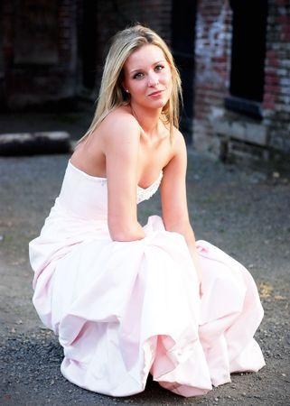 woman kneeling: Attractive blond woman kneeling down in a bridesmaids dress. Vertically framed shot.