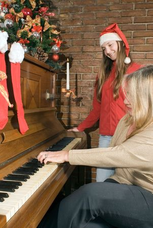 Grandmother playing the piano while her granddaughter (wearing a santa hat) looks on photo