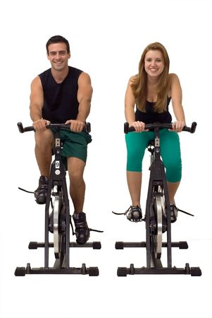 Attractive Couple on exercise bikes smiling. Isolated against a gray studio background. Vertically framed shot