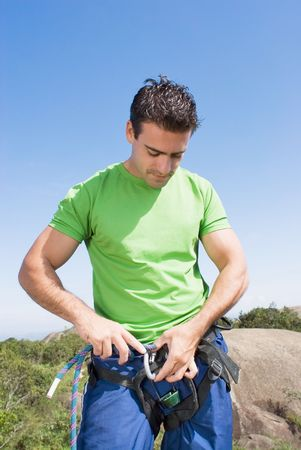 Athletic young man attaching a climbing rope to his climbing harness.
