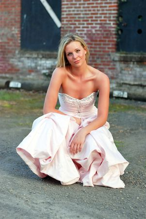 Vertically framed outdoor shot of an attractive bridesmaid crouching down in front of red brick wall. Stock Photo - 3116581