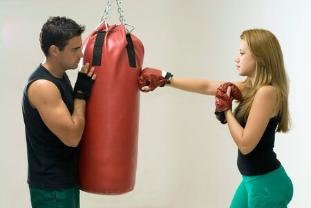 Attractive woman working out with boxing gloves and a heavy punching bag with her trainer.