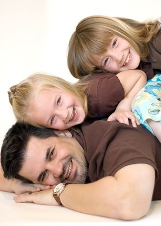 family fun day: Doting father and his two adorable daughters posing together in a studio. Vertically framed shot