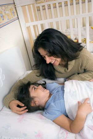 Mother tucking her adorable daughter in for the night Stock Photo