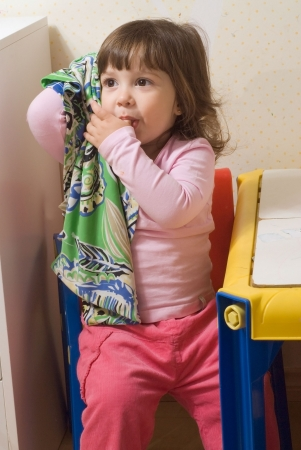 Cute little girl sucking her thumb and holding onto her blankie.