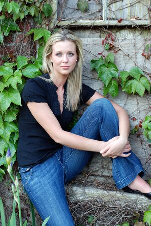 Attractive young blond woman casually dressed sitting by an ivy covered stone and brick wall