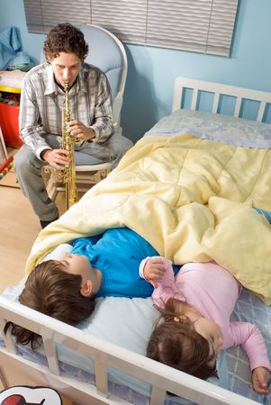 Vertically framed shot of a father playing soprano saxophone for his children in a bedroom during bedtime. Stock Photo - 3121351