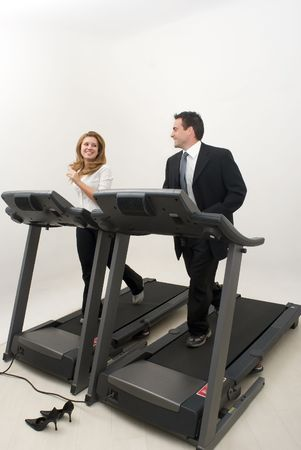 Male and female businesspeople running on treadmills while looking at each other and smiling photo