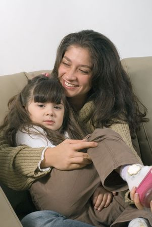 A smiling mother cuddling her daughter on a sofa. photo