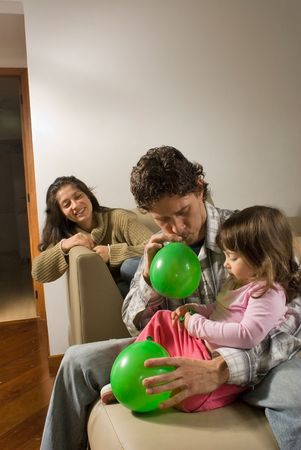 Father blowing up balloons for his daughter sitting next to him, mother smiling in background. photo