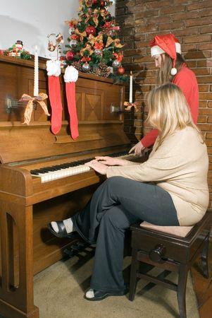 carols: Mother and daughter sitting at the piano singing Christmas carols. Vertically framed shot.