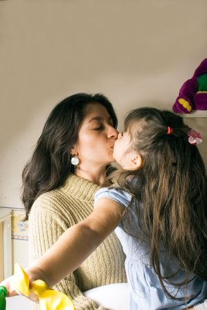 A mother kissing her daughter.