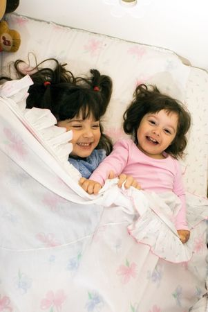 Two smiling little girls playing in bed. photo
