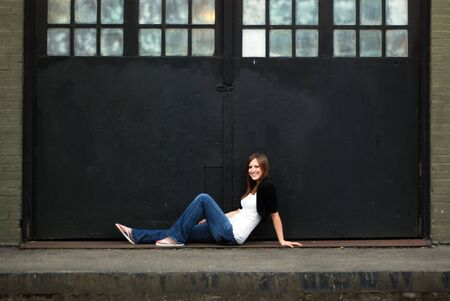 abandoned warehouse: Young attractive brunette stretched out in front of a warehouse door. Horizontally framed wide-angle shot. She is smiling and casually dressed.