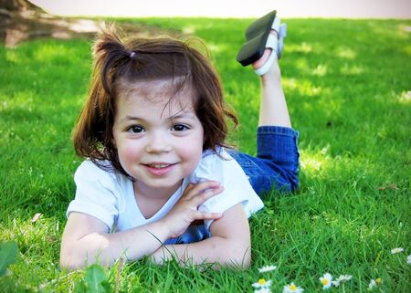 Adorable little girl lying casually in the grass on a sunny summer day. Horizontally framed shot. She is smiling at the camera.