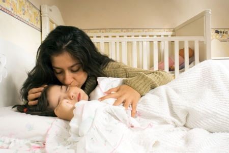 Attractive mother kissing her sleeping daughters forehead. Horizontally framed shot