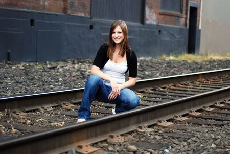 abandoned warehouse: Young attractive brunette crouching down by some railway tracks in an old industrial area Stock Photo