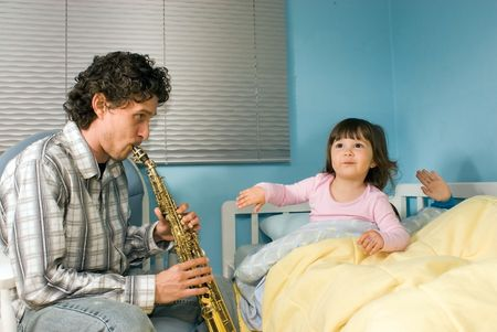 Horizontally framed shot of a father playing a soprano saxophone for his children in a bedroom. photo