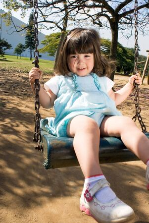 Cute little girl playing on a swing on a sunny day. Vertically framed shot. photo