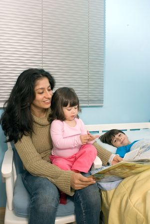 Vertically framed shot a smiling mother reading a book to a daughter sitting on her lap and son lying in bed. photo