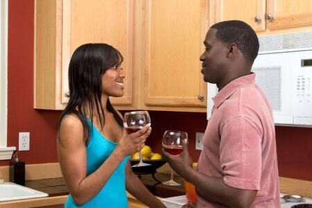 soulmate: Attractive smiling young African American couple looking at each other standing in a kitchen holding wine glasses.   Stock Photo