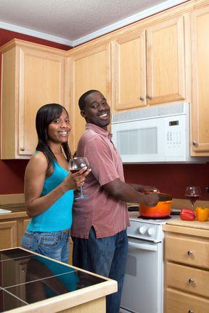 mujeres cocinando: Atractivos j�venes riendo African American joven cocina la cena junto potable y vino tinto. Vertical enmarcada disparo con el hombre y la mujer mirando hacia la c�mara.