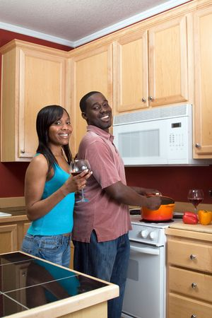 Attractive young laughing African American couple cooking dinner together and drinking red wine. Vertically framed shot with the man and woman looking towards the camera.
