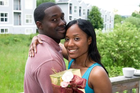 Attractive young woman hugging a man with one arm and holding a present in the other arm.   photo