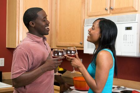 soulmate: Attractive laughing African American young couple looking at each other standing in a kitchen clinking wine glasses, in a toast.
