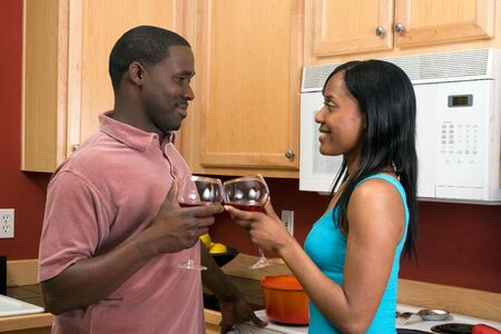 Attractive smiling young African American couple looking at each other standing in a kitchen clinking wine glasses, in a toast.   photo