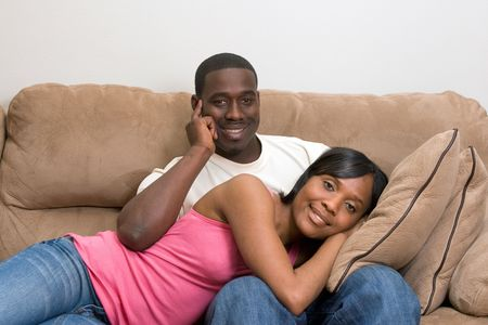 soulmate: Cute young African American Couple relaxing together in their living room.  Stock Photo