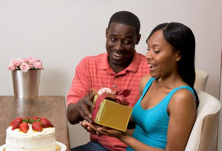 Young attractive african american couple exchanging gifts at their dining table.