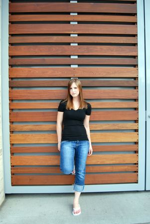 angst: Vertically framed outdoor shot of a teenage girl leaning against a Teak paneled wall.