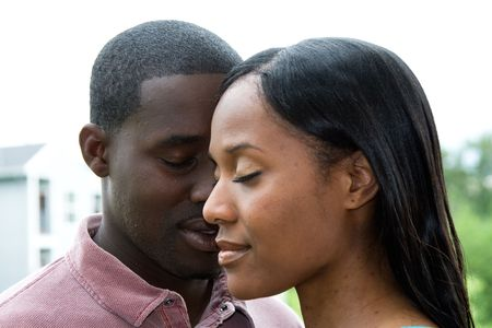 new love: Attractive young couple, with their eyes, in a close-up tranquil embrace.  Horizontally framed portrait shot.