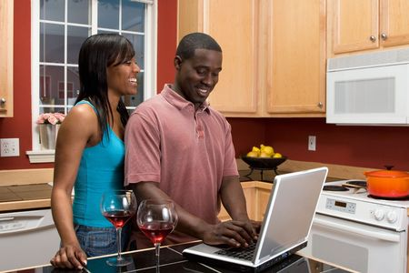 Attractive young African american couple laughing together in their kitchen while looking at something on a computer screen. photo