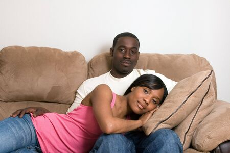 couple on couch: Attractive young african american couple relaxing together on their living room couch. Stock Photo