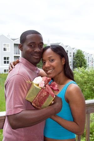 soulmate: Attractive young woman hugging a man with one arm and holding a present in the other arm.