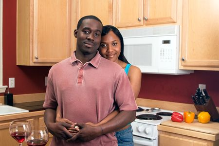 Attractive african american couple standing and hugging in their kitchen with a neutral expression on their faces. Stock Photo