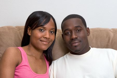 couple on couch: Attractive young african american couple sitting together on their living room couch. Stock Photo