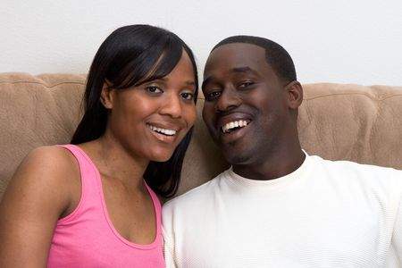 Attractive young african american couple sitting together on their living room couch.  photo
