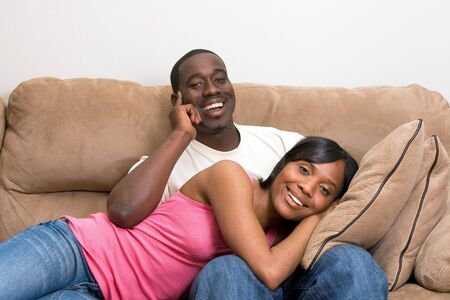 Cute young African American Couple relaxing together in their living room.  Stock Photo