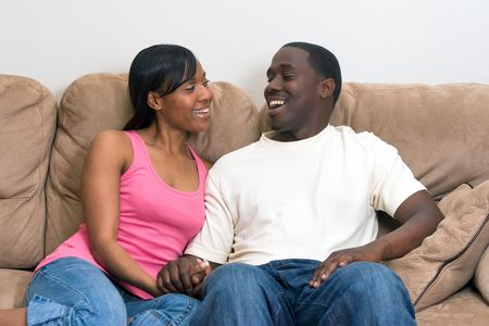 soulmate: Young, attractive african american couple relaxing together on their couch.  Stock Photo