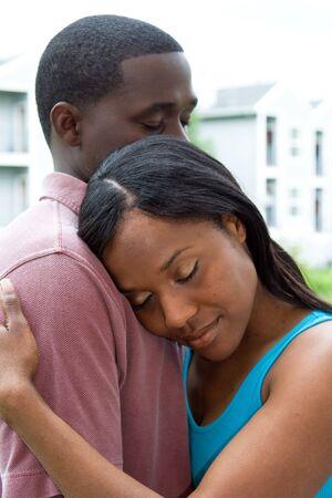 negras africanas: Atractivo joven pareja en un abrazo, con el WOMANS cabeza descansando sobre el hombro Mans. Verticalmente retrato al aire libre enmarcada en un tiro cubierta.