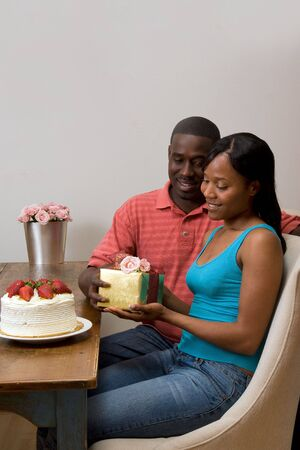 Young attractive african american couple exchanging gifts at their dining table. Vertically framed shot. photo