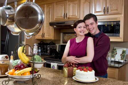 Attractive couple hugging in the kitchen by a counter covered with a cake and a present. The pair are laughing heartily while looking at the camera. Horizontally framed shot. photo