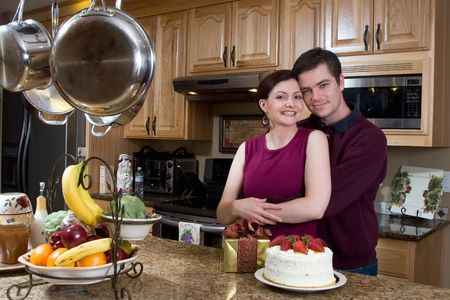 Attractive couple hugging in the kitchen by a counter covered with a cake and a present. They have a neutral expression on their faces and they are looking at the camera. Horizontally framed shot. photo