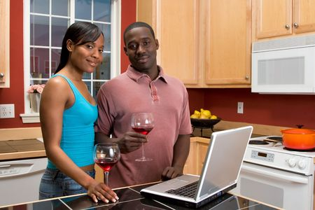 Attractive African American couple, with neutral expressions, standing in a kitchen, holding wine glasses, while using a laptop.  Horizontally framed shot with the man and woman looking at the camera. photo
