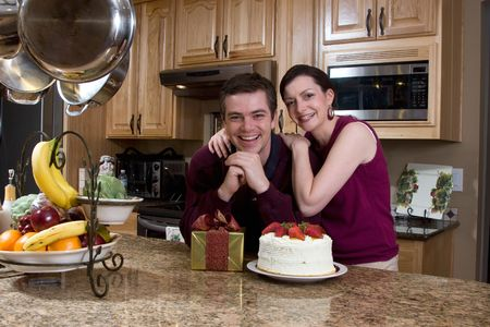 Attractive couple leaning on their kitchen counter which is covered with a cake and a present. They have a huge smile on their faces and are looking at the camera. Horizontally framed shot. photo