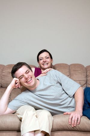 Couple lounging together on their living room couch. He is lying in her lap. Both are laughing at the camera. Vertically framed shot.