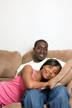 soulmate: Attractive smiling young couple relaxing on a sofa.  The man is sitting, and the woman lying with her head in his lap.  Vertically  framed shot with copy-space above the sofa. Stock Photo